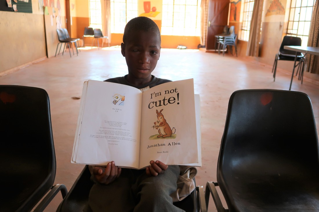 "a young boy poses shyly with his favorite book, called ""I'm Not Cute"""