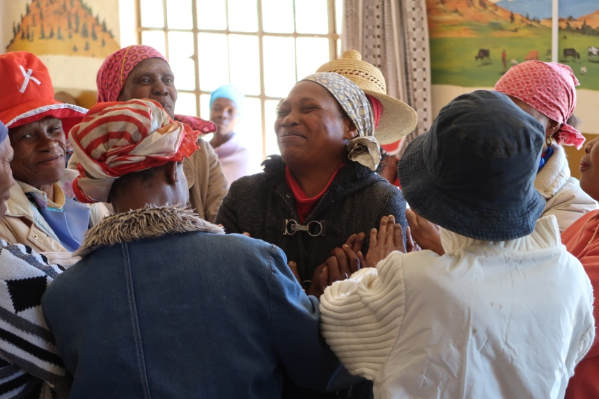 a woman is smiling, surrounded by other supportive women during a trust exercise for the Malealea Development Trust's HIV/AIDs support group in Lesotho, Southern Africa