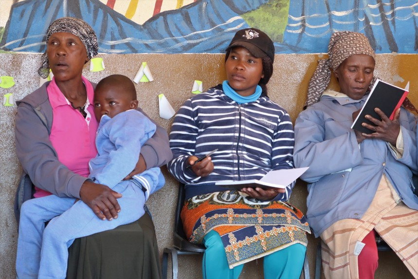 a mother holds her young son, while two other women are taking notes on the discussion at the Malealea Development Trust's HIV/AIDs support group discussion in Lesotho, Southern Africa