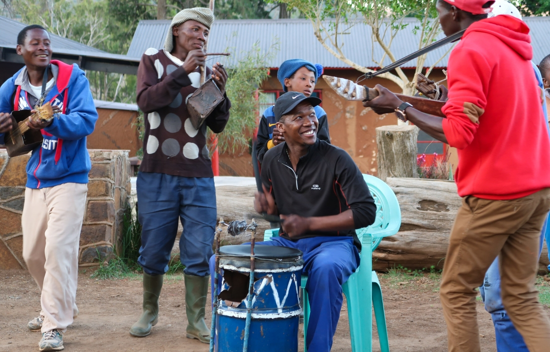 a group of musicians perform outside at the Malealea Lodge on homemade traditional Basotho instruments, photo by Kelly Benning