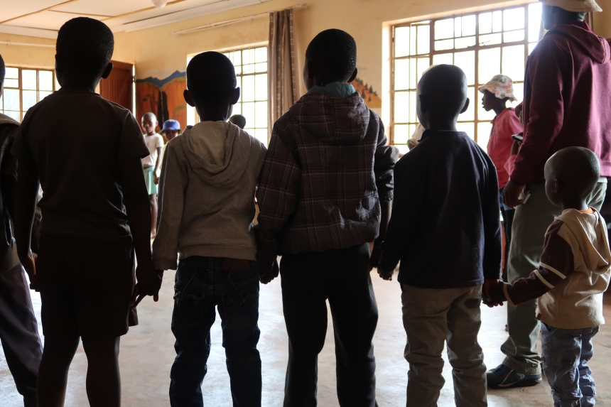 the silhouettes of five small boys holding each other's hands during the Malealea Development Trust's Children's Day in Lesotho, Southern Africa