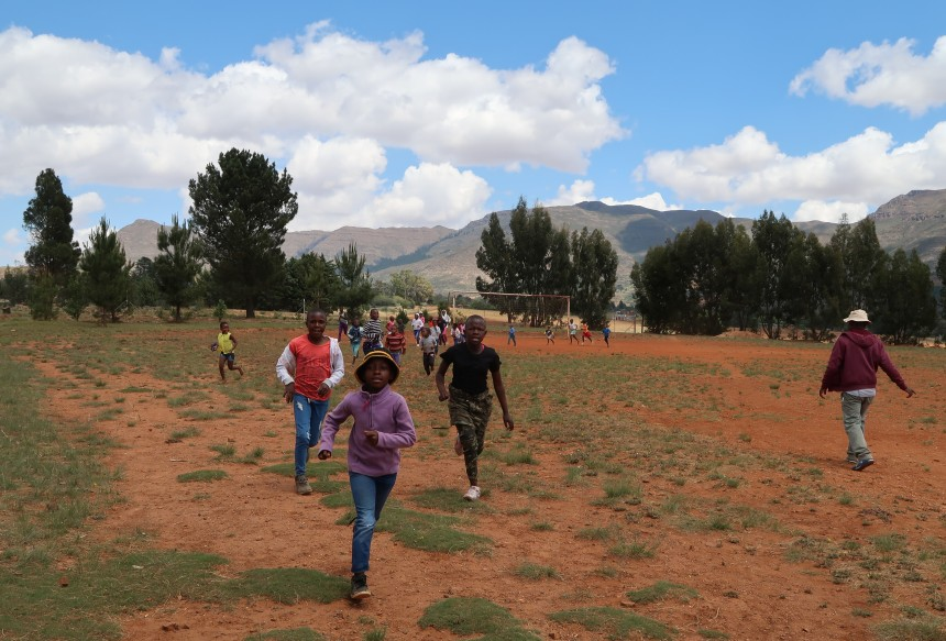 children run laps around the soccer field during Malealea Development Trust's Children's Day in Lesotho, Southern Africa