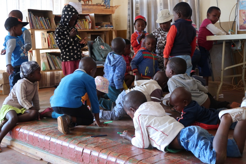 a group of children lie on the floor coloring at the Malealea Development Trust's Children's Day in Lesotho, Southern Africa