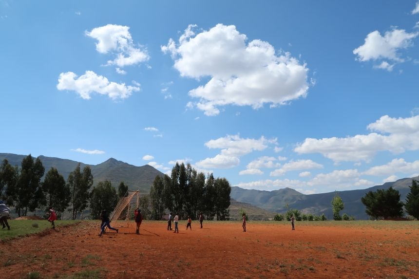 a group of children play soccer under a brilliant blue sky, surrounded by green mountains in Malealea, Lesotho, Southern Africa