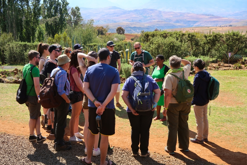a group of tourists meets with a Malealea Development Trust staff member before going on a guided Village Tour in Lesotho, Southern Africa, photo by Kelly Benning