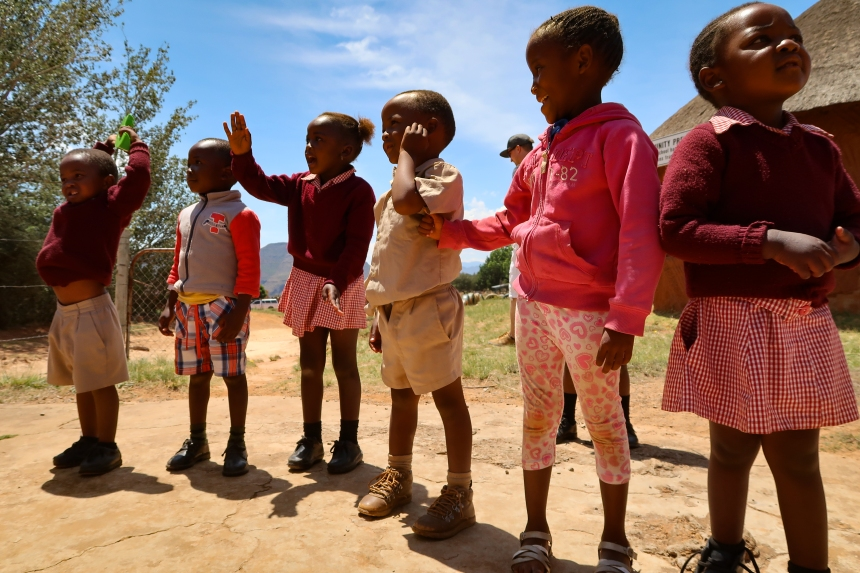 a row of smiling preschoolers wave to visitors outside a Malealea preschool, Lesotho, Southern Africa, photo by Kelly Benning