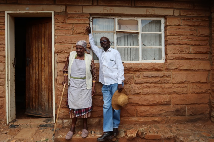 Albert Musi and his mother stand outside of the house his father built for them