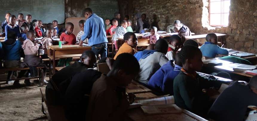 a crowd of student sitting at desks in a small, cramped rural classroom in Malealea, Lesotho