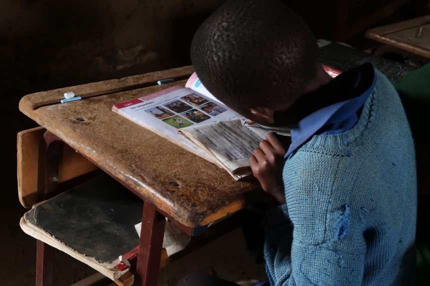 a young girl writes in a notebook at a school desk in Malealea, Lesotho