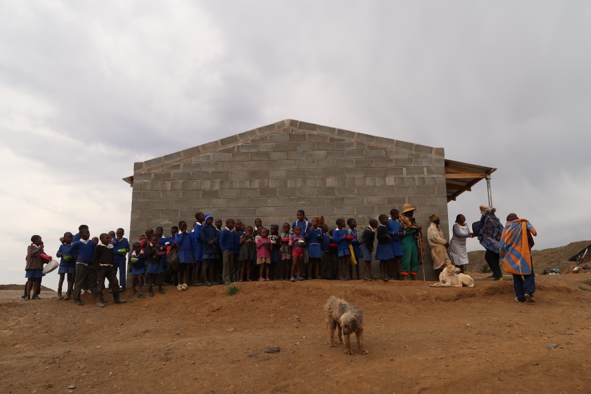 a group of children stand outside their school on a cloudy day in Malealea, Lesotho