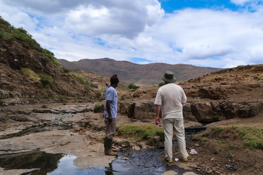 A local man shows a Dutch fundraiser a second source that could be converted into a pipeline for Ha Raboletsi, a village in Roma, Lesotho, Southern Africa, photo by Kelly Benning
